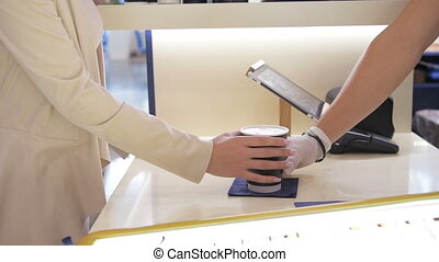 Customer buying his take-away coffee with smartphone in a...