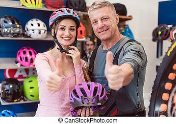 Customer choosing bicycle helmet in a shop