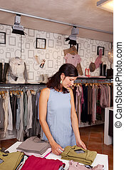 Customer Choosing Clothes At Desk In Boutique