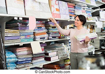 customer demonstrating bed sheets - Positive woman ...