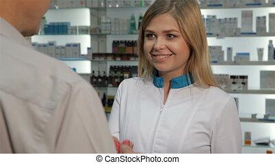 Customer gets blister of pills from pharmacist at the drugstore