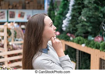 customer girl choosing Christmas tree for the new year -...