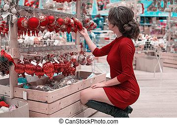 customer girl choosing decoration balls for Christmas tree -...