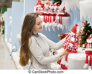 customer girl choosing gifts for Christmas and New Year -...