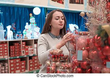 customer girl choosing red Christmas tree decoration balls....