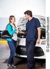 Customer Giving Car Keys To Technician At Garage