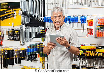 Customer Holding Digital Tablet In Hardware Store