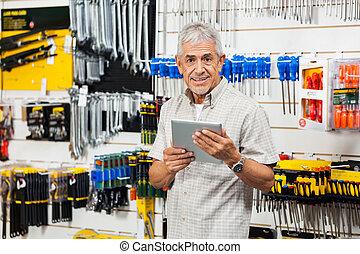 Customer Holding Digital Tablet In Hardware Store
