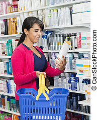 Customer Holding Shampoo Bottle In Pharmacy