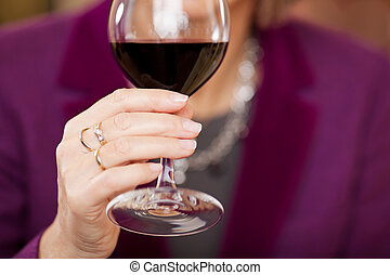 Customer Holding Wine Glass At Restaurant Table - Midsection...