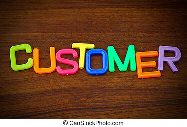 Customer in colorful toy letters on wood background