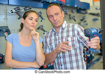 customer in hardware store buying drill