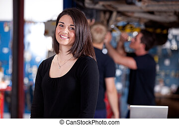 Customer in Mechanic Shop - A happy woman customer in a...