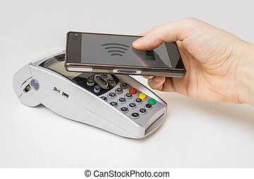 Customer is paying with smartphone using NFC technology and paym