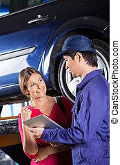 Customer Looking At Mechanic Holding Digital Tablet