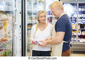 Customer Looking At Salesman Assisting Her In Supermarket