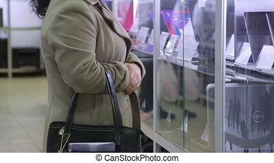Customer looks at prices of laptops in electronics store