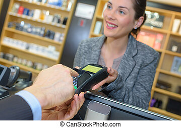 customer making payment through smartwatch in the perfume shop