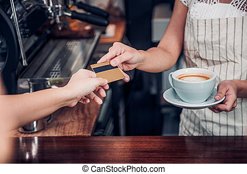 customer pay coffee drink with credit card to barista,Close...