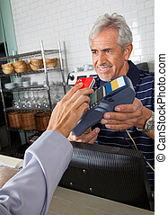 Customer Paying Through Mobile Phone In Store