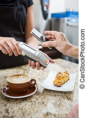 Customer Paying using NFC - Customer paying for coffee using...