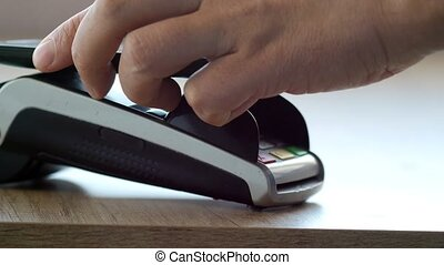 Customer paying with NFC technology by mobile phone on POS...