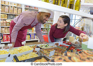 customer pointing to dish with sales assistant at deli...