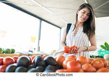 Customer Selecting Fresh Tomatoes In Supermarket