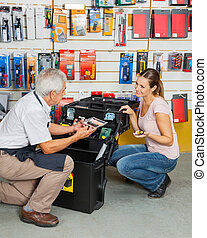 Customer Selecting Tools While Salesman Assisting Her In Store