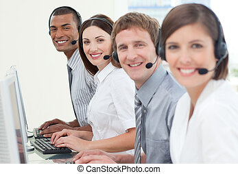 Customer service agents with headset on smiling at the...