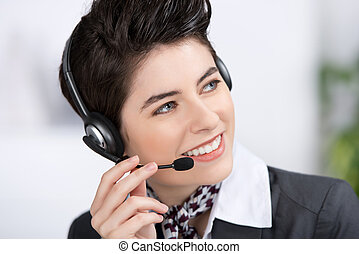 Customer Service Executive Conversing On Headset In Office