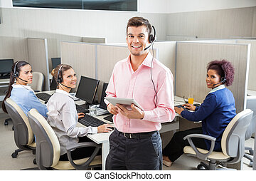 Customer Service Executive Holding Tablet Computer In Call Cente