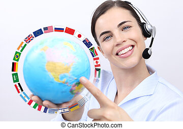 Customer service operator woman with headset smiling, holding globe, international flags, contact us concept