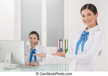 Customer service representative at work. Cheerful young female customer service representative pointing her coworker working at the computer and smiling