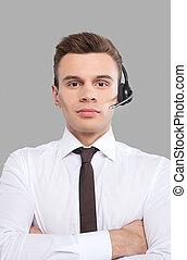 Customer service representative. Cheerful young man in formalwear adjusting his headset and smiling at camera while standing against grey background