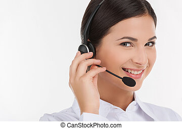 Customer service representative. Portrait of beautiful young female customer service representative in headset looking at camera and smiling while isolated on white
