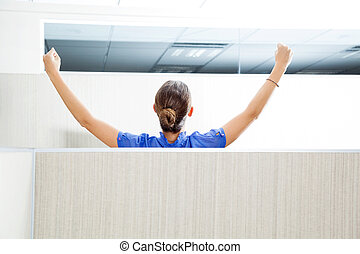 Rear view of female customer service representative with arms raised in cubicle