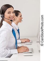 Customer service representatives at work. Two cheerful young female customer service representatives in headset working at the computer and smiling