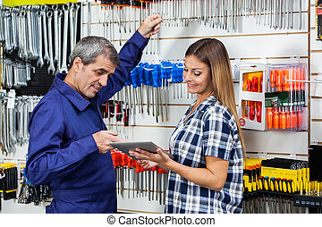 Customer Showing Digital Tablet To Vendor In Hardware Store