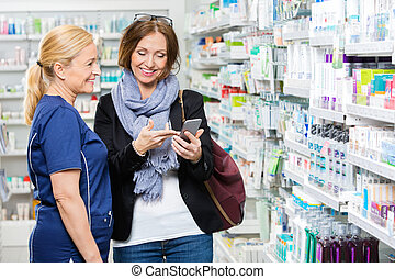 Customer Showing Mobile Phone To Pharmacist In Pharmacy