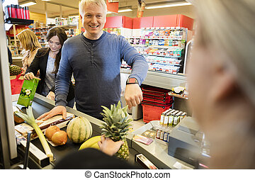Customer Showing Smartwatch To Cashier In Supermarket