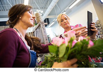 Customer Showing Something On Digital Tablet To Florist