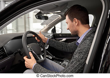 Customer sitting in driver's seat of car cabin.