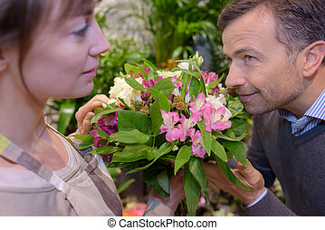 Customer smelling bouquet of flowers