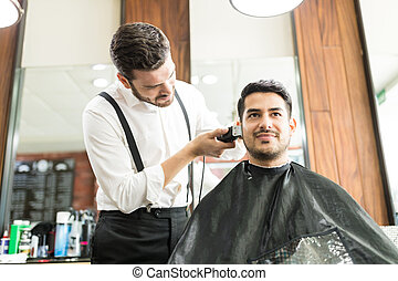 Customer Smiling While Barber Trimming His Hair In Shop