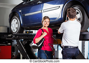Customer Standing With Mechanic Refilling Tire
