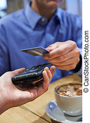 Customer Using Contactless Payment In Coffee Shop
