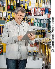 Customer Using Digital Tablet In Hardware Store