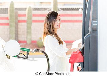 Customer Using Fuel Pump At Gas Station
