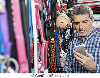 Customer Using Mobilephone While Buying Pet Leash